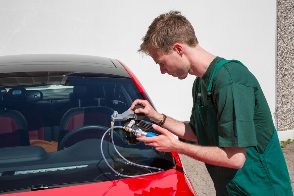 professional auto glass expert working on auto glass replacement