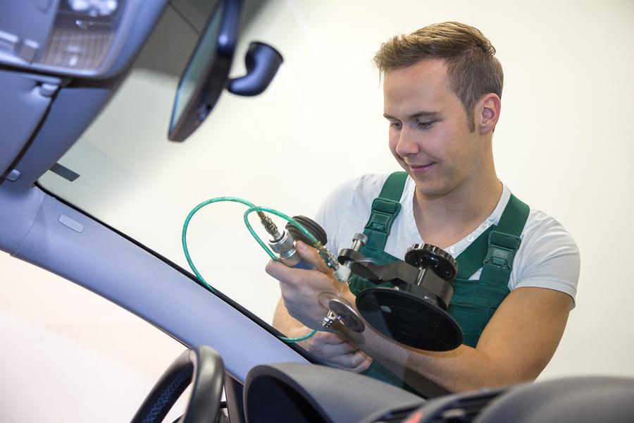 professional auto glass expert working on leak repair