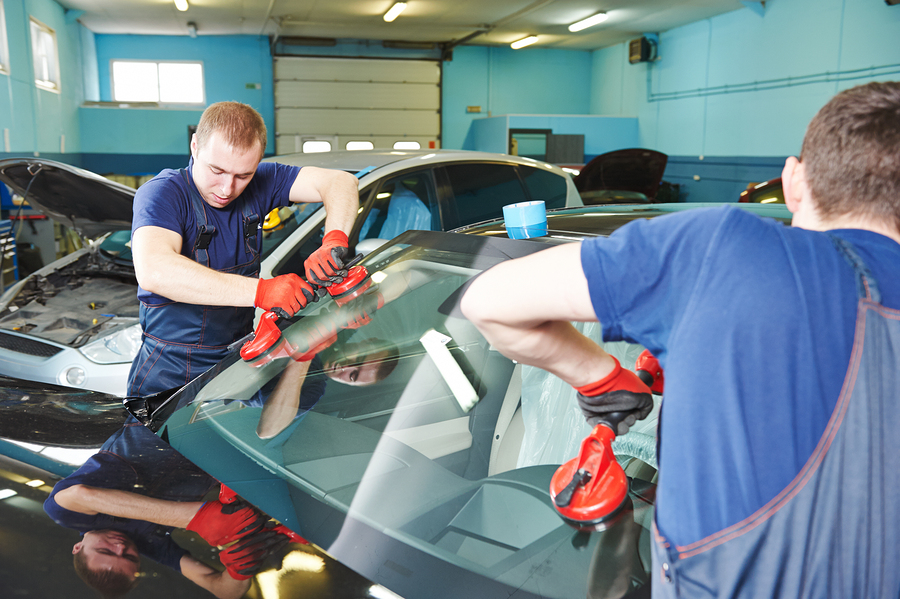professional auto glass expert working on windshield replacement